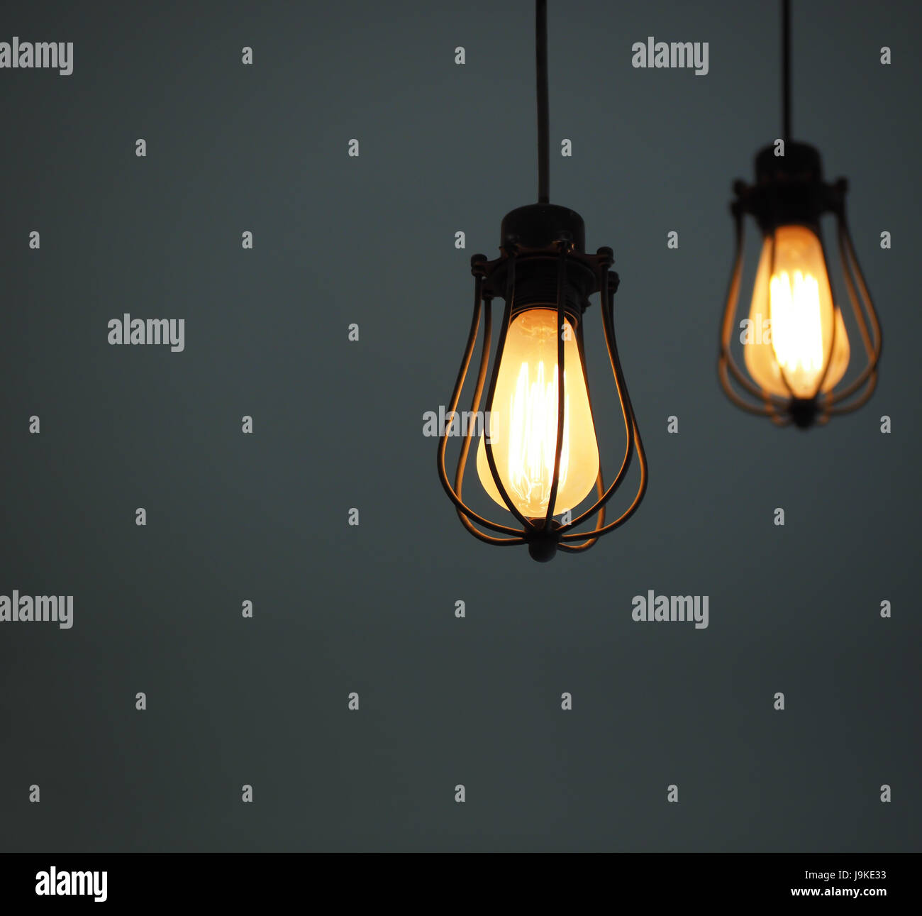 Close up of yellow illuminated hanging light bulbs on grey plain background with text space - Stock Image