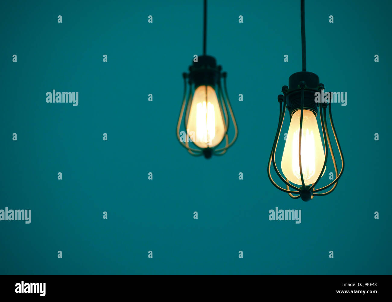 Illuminated Hanging Light Bulbs On Blue Plain Background With Free Text  Space