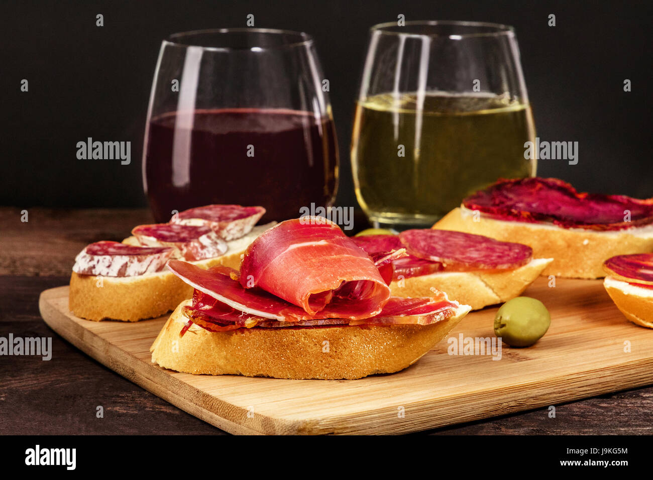 A photo of embutidos tapas, sandwiches with jamon, salchichon, lomo, and other Spanish sausages, with glasses of - Stock Image