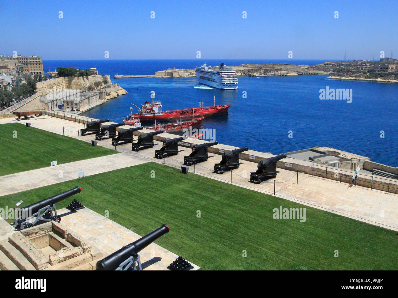 Merchant shipping and cruise ship arriving in Grand Harbour, Valletta, Malta from gun Saluting Battery platform - Stock Image