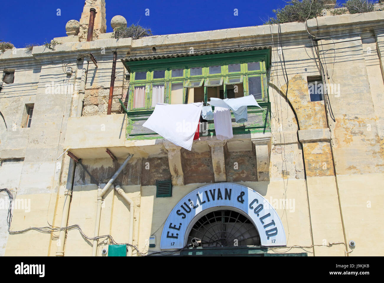 Old merchant house with balcony about warehouse area, Valletta, Malta F E Sullivan ship supply business premises - Stock Image