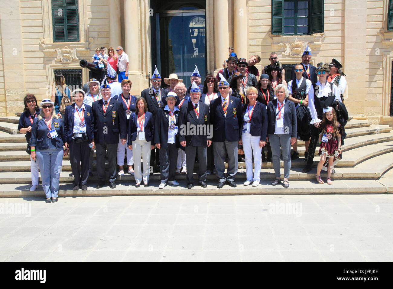 Tour group photo of carnival organisers on steps of Auberge de Castille palace in city centre of Valletta, Malta - Stock Image