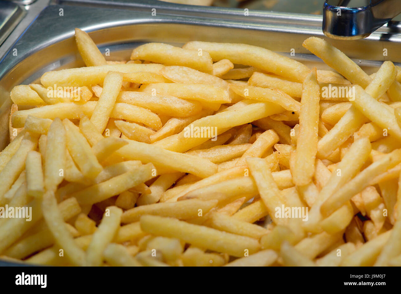 Golden fried potatoes fries on the counter of the restaurant fast food. Closeup. - Stock Image