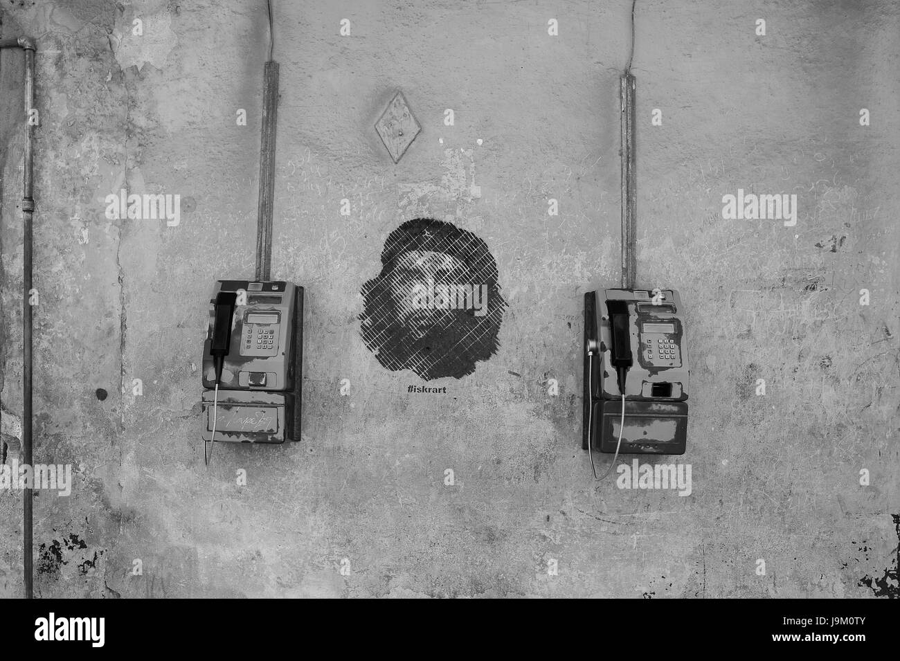 Payphones hanging on wall with ernesto che guevara stencil graffiti painting in Havana, Cuba - Stock Image