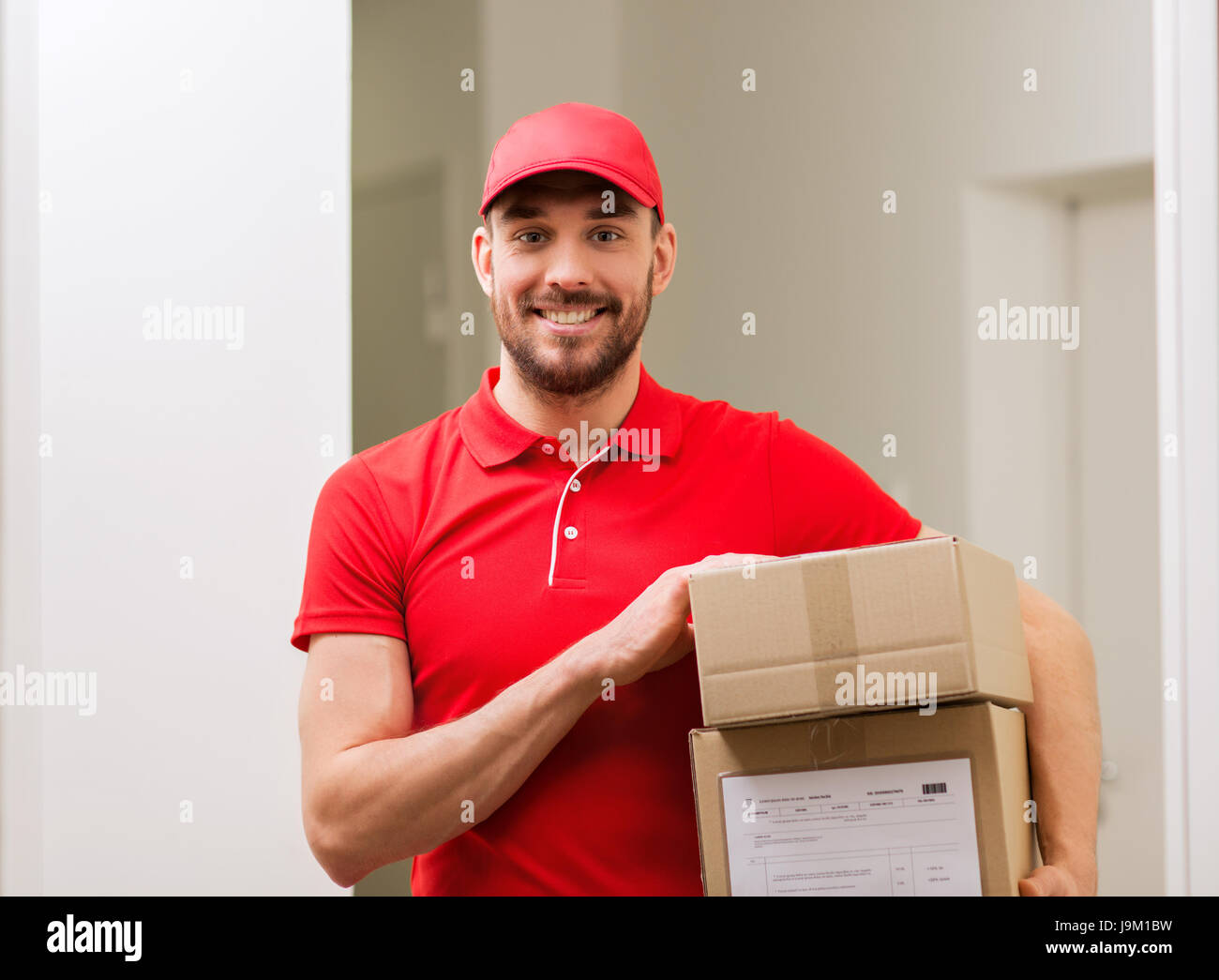 delivery man with parcel boxes in corridor - Stock Image