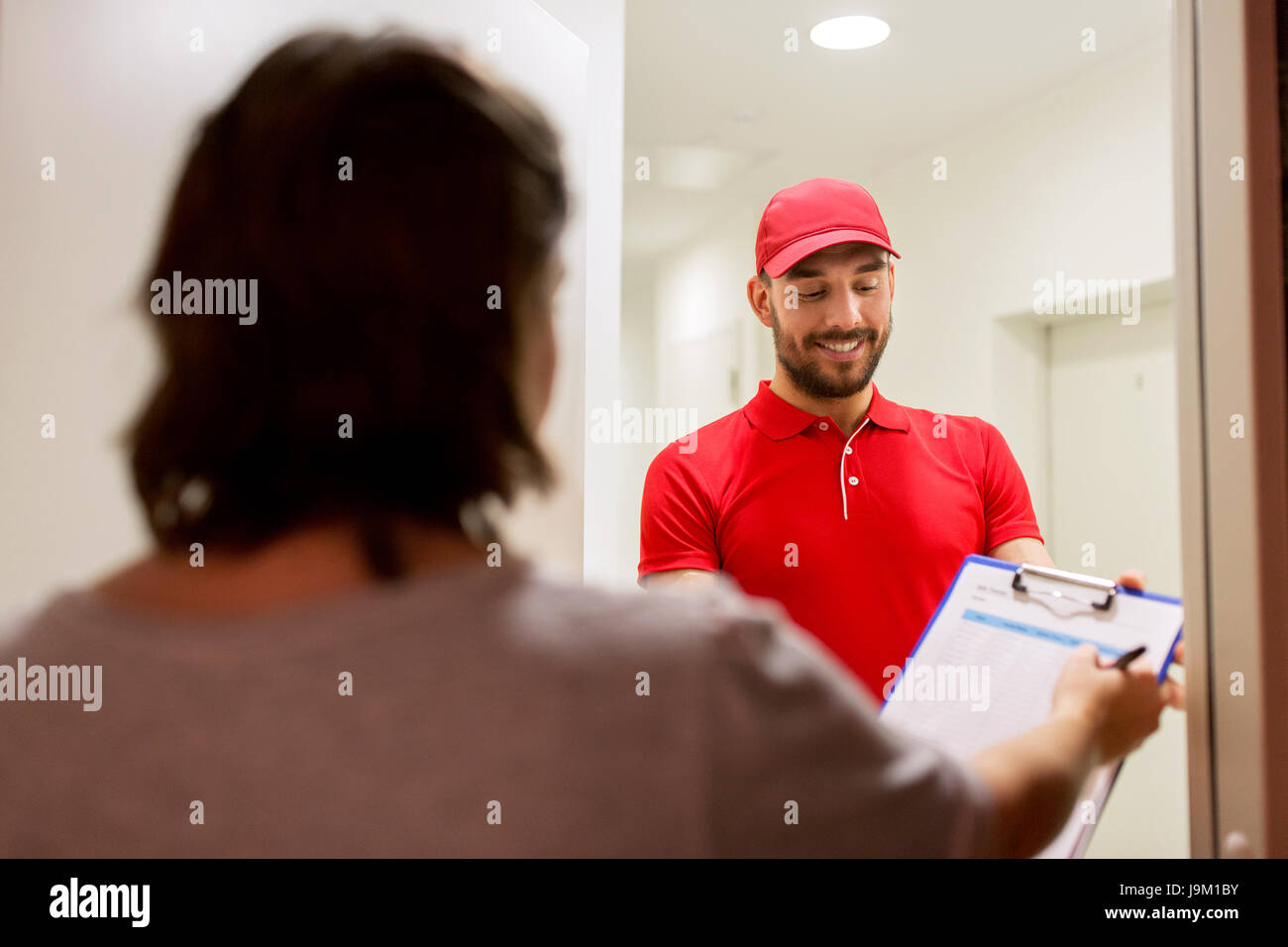 deliveryman with clipboard at customer home - Stock Image