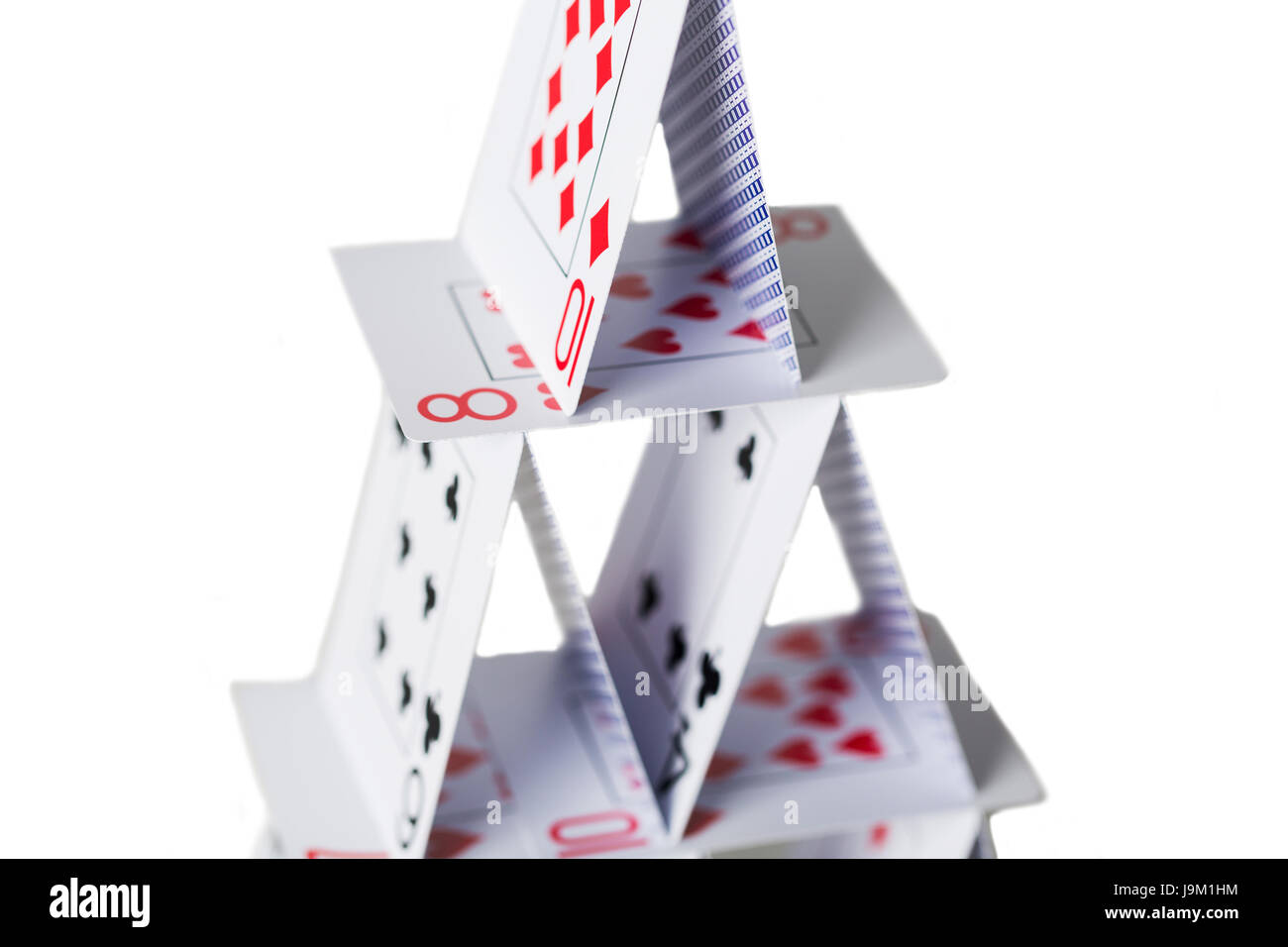 house of playing cards over white background - Stock Image