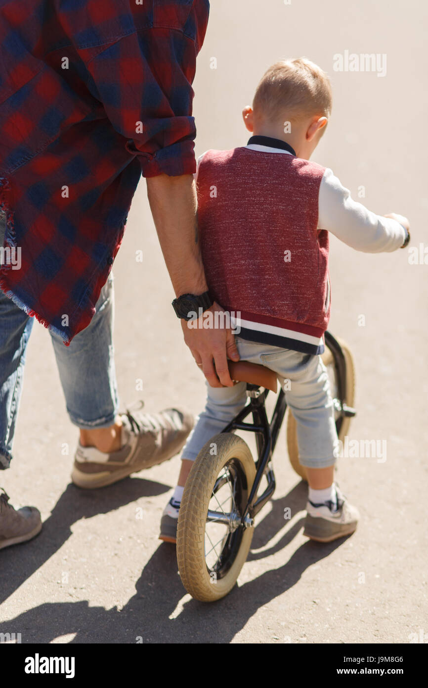 Dad teaches son to ride - Stock Image