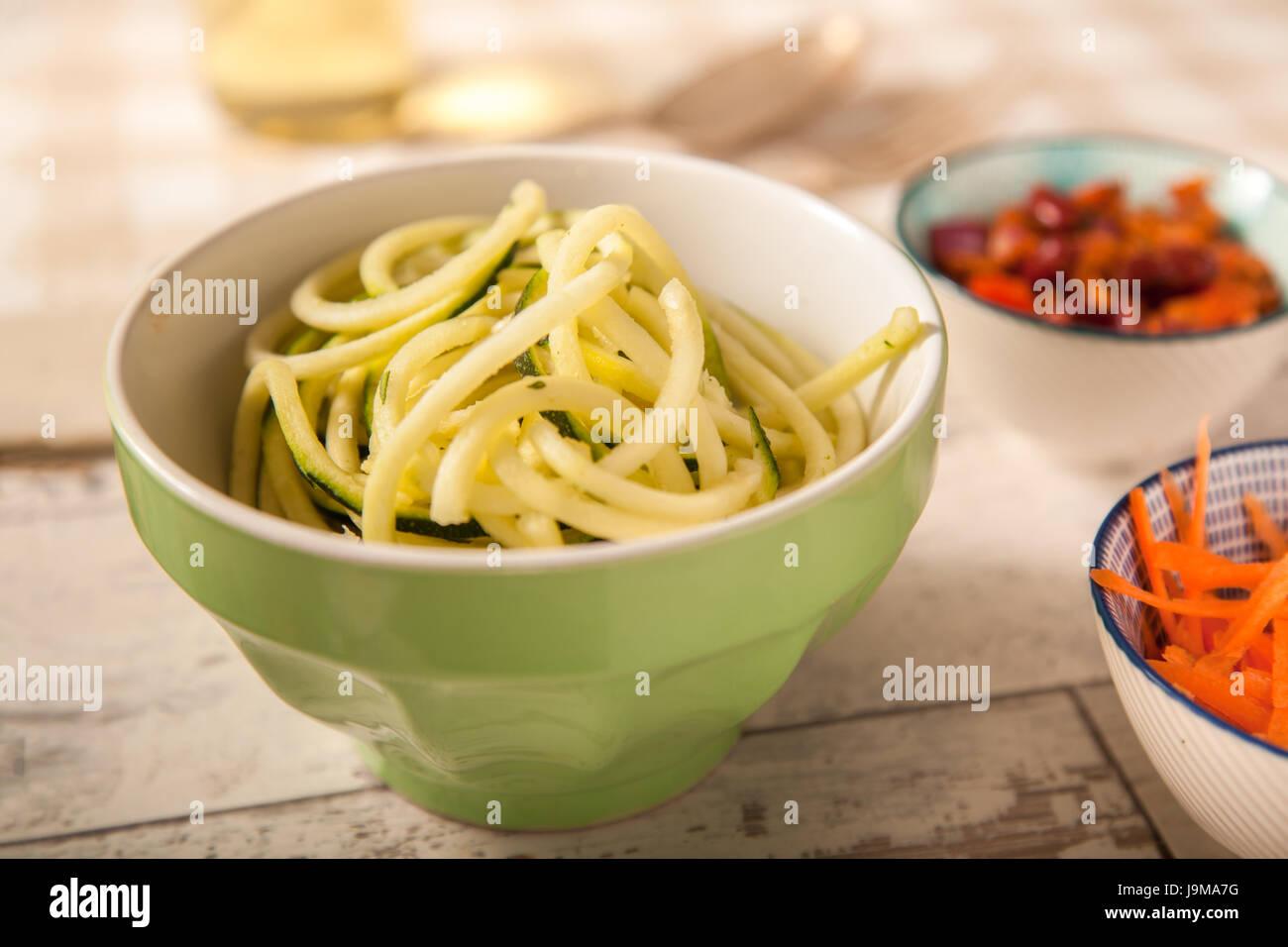 Courgette Spaghetti in a green Bowl Stock Photo