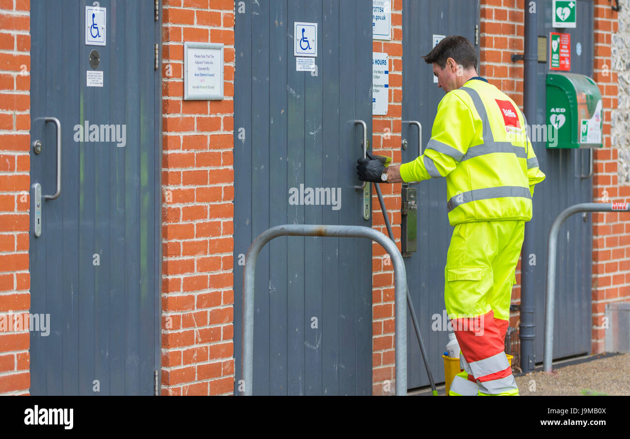 Public toilet attendant entering a toilet to clean it. Toilet cleaner. - Stock Image