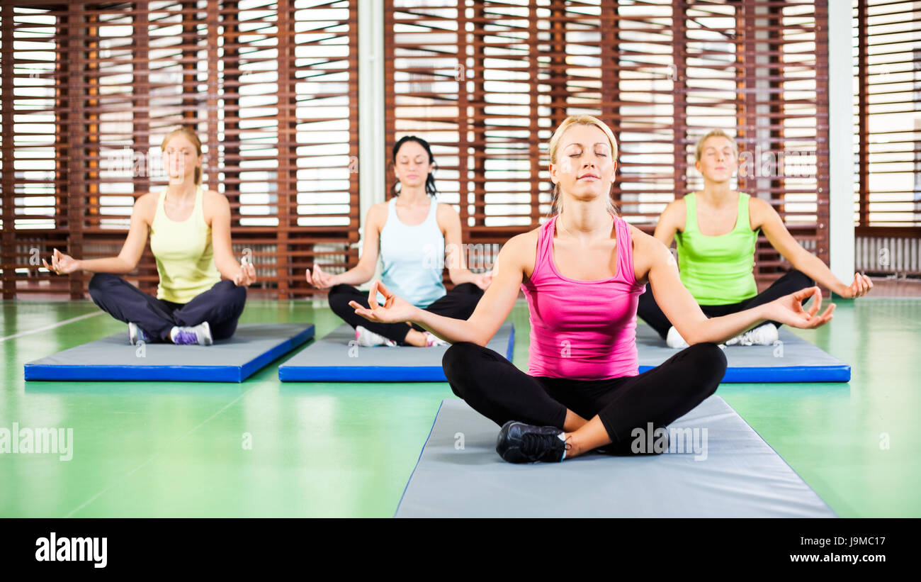 Four girls meditating after fitness training in gym - Stock Image