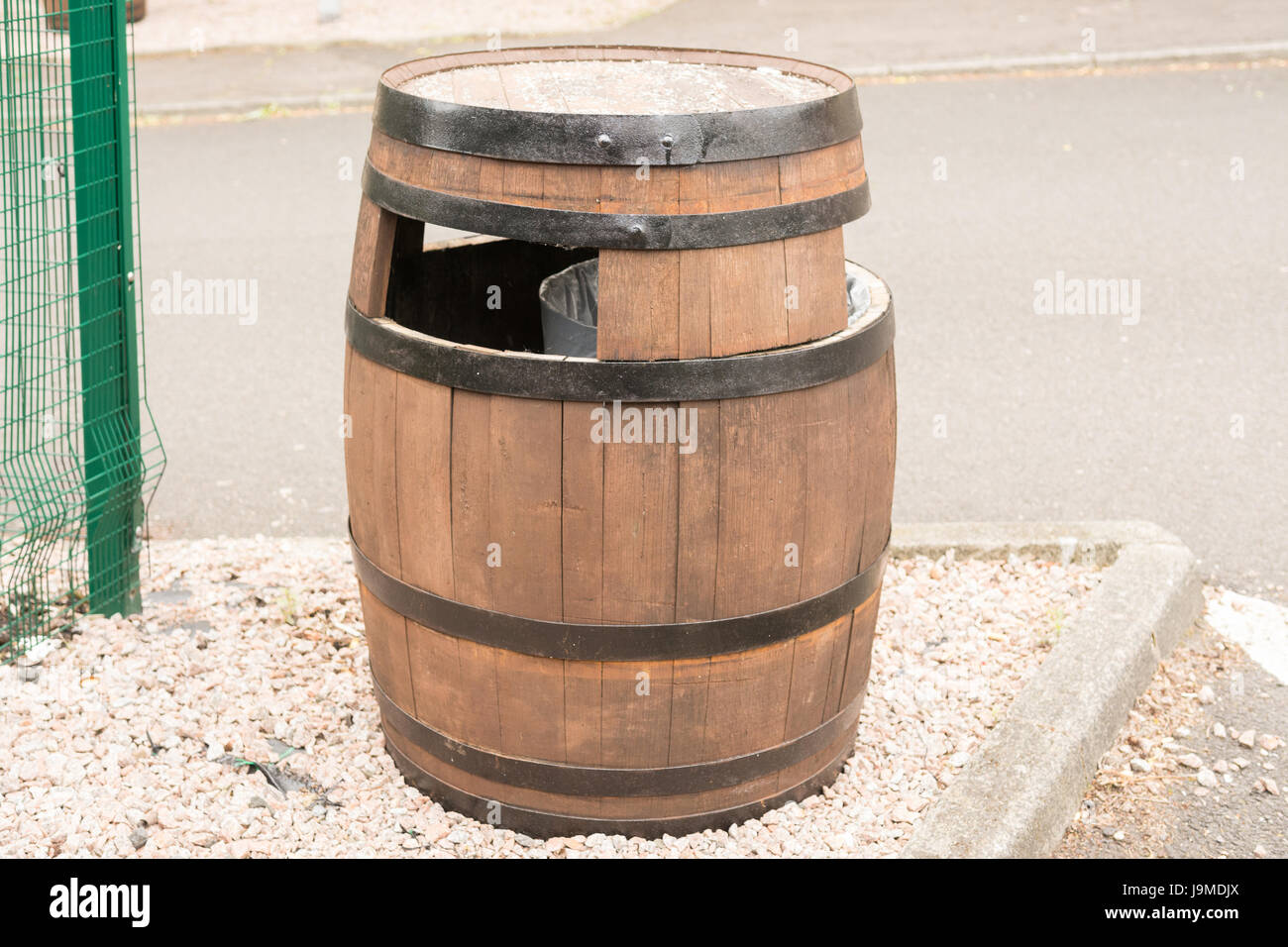upcycling - upcycled recycled whisky whiskey barrel being used as a rubbish bin - Stock Image