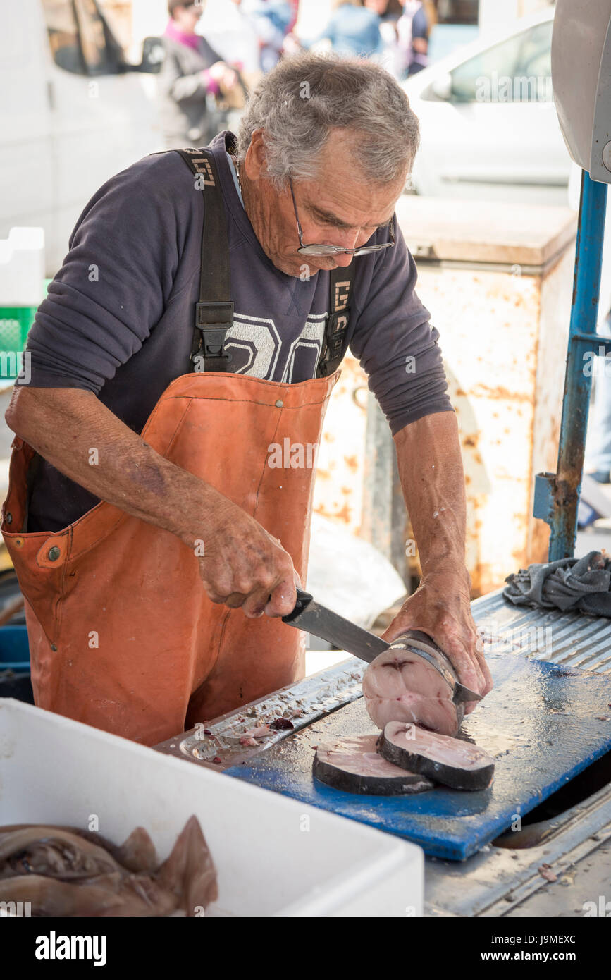 A fishmonger cutting up fish on a market stall in the market at Marsaxlokk Malta - Stock Image