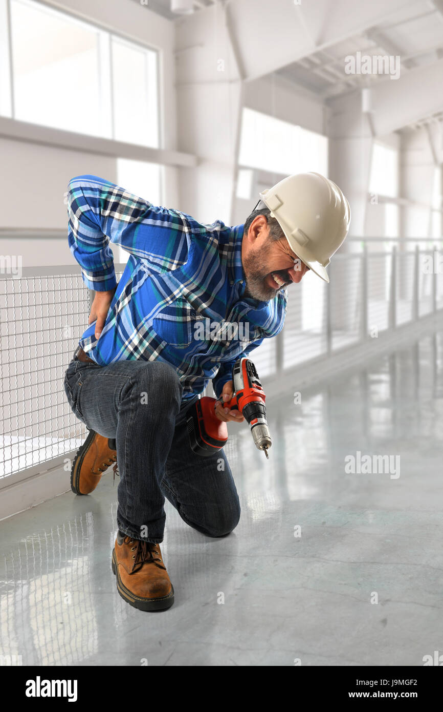 Hispanic worker suffering back injury inside building - Stock Image