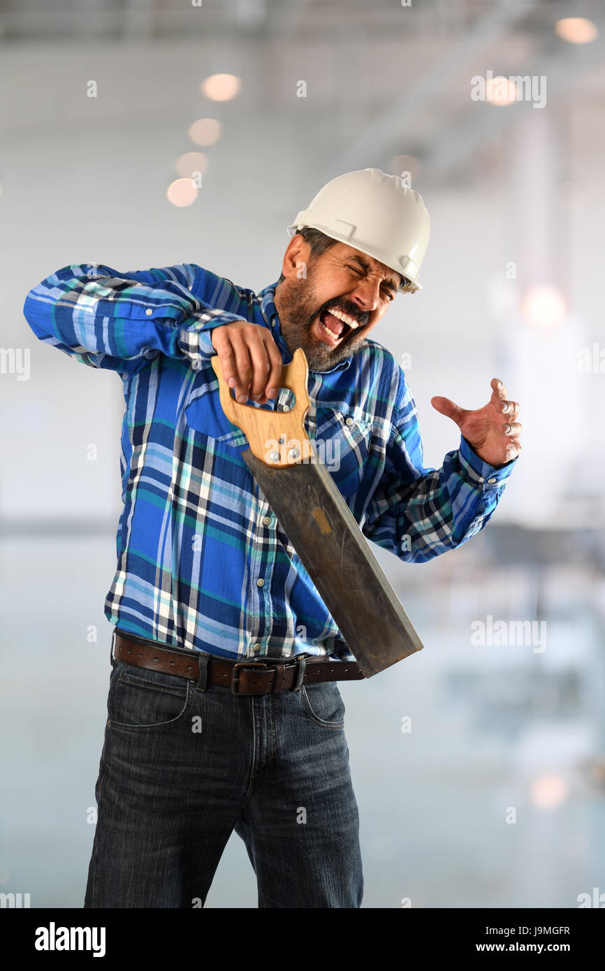 Hispanic worker suffering accident with saw inside building - Stock Image