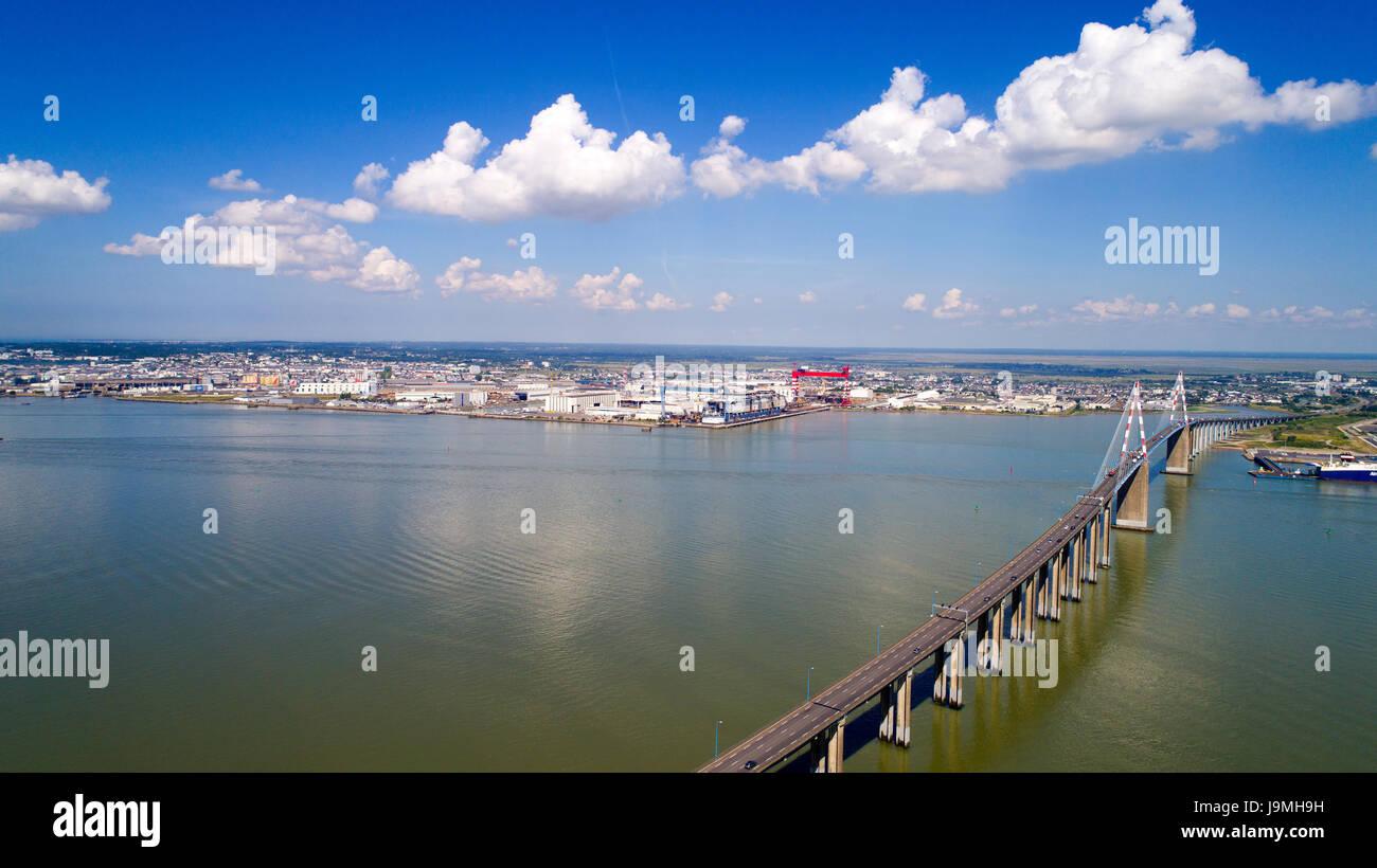 The Saint Nazaire bridge and the Atlantic shipyards in Loire estuary, France - Stock Image