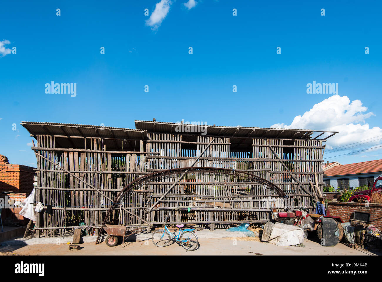 Farmyard near Xifeng, Liaoning, China. The large wooden structure is used for drying and storing corn cobs which - Stock Image