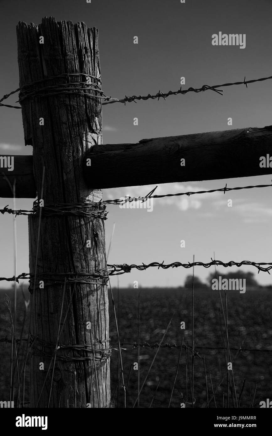 High contrast artistic monochrome image of an old wooden barbed wire fence in rural Nebraska, USA. - Stock Image