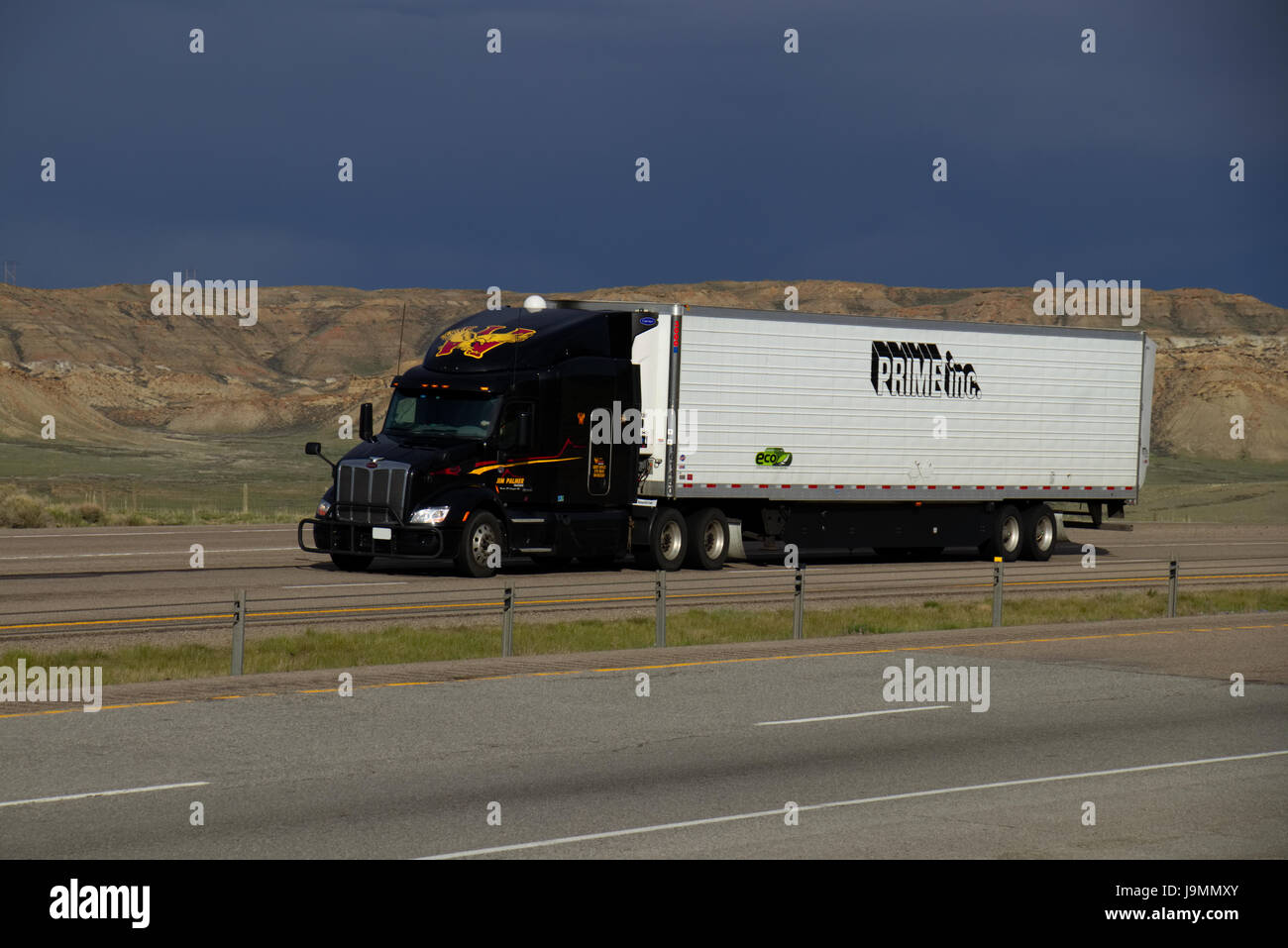 Black 'Wil Trans' Peterbilt Semi-Truck pulling a white 'Prime Inc.' Trailer along a rural US Highway. - Stock Image