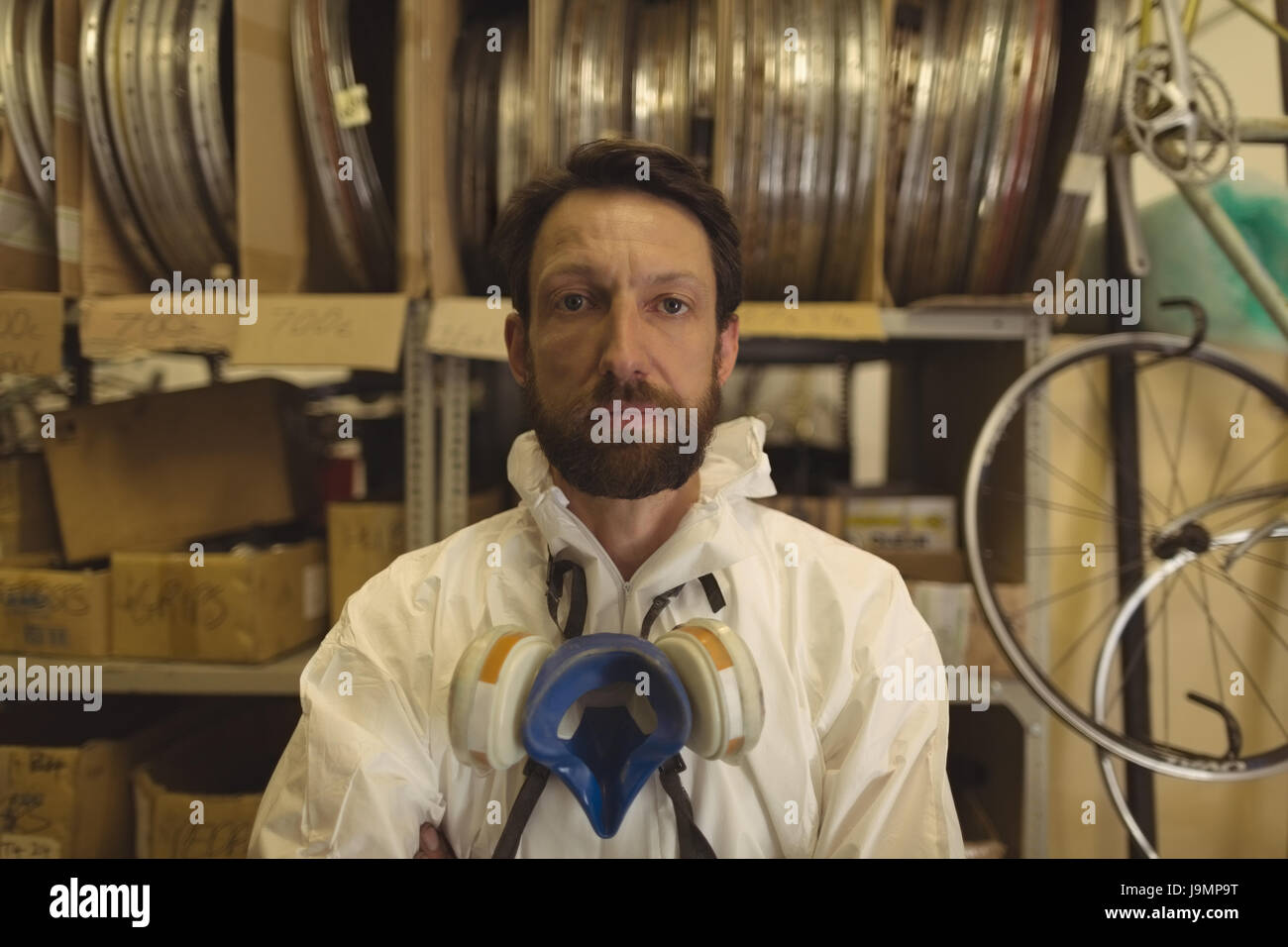 Portrait of painter with gas mask staning at bicycle workshop - Stock Image