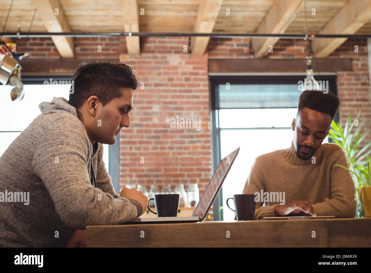 6f8a6bad27 Gay couple using digital tablet and laptop while having coffee at home -  Stock Image