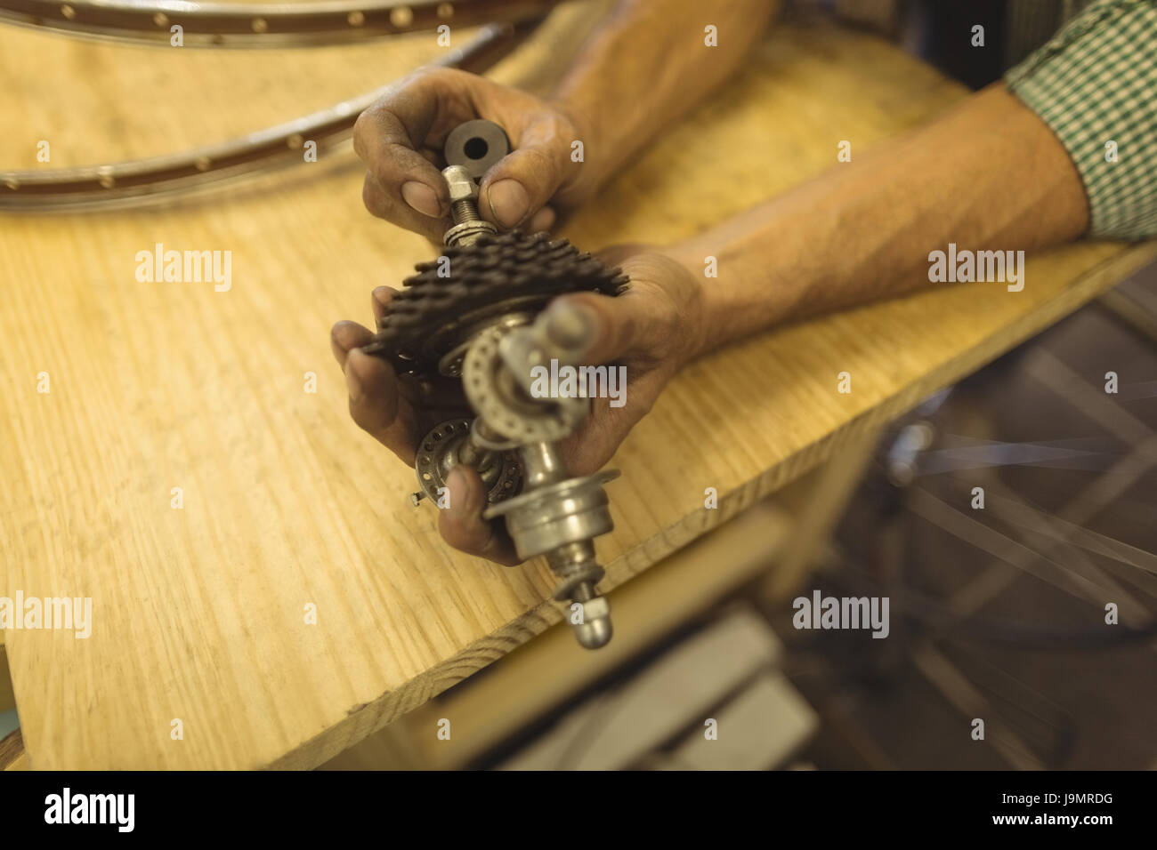 Cropped hands of worker repairing bicycle gear on table at workshop Stock Photo