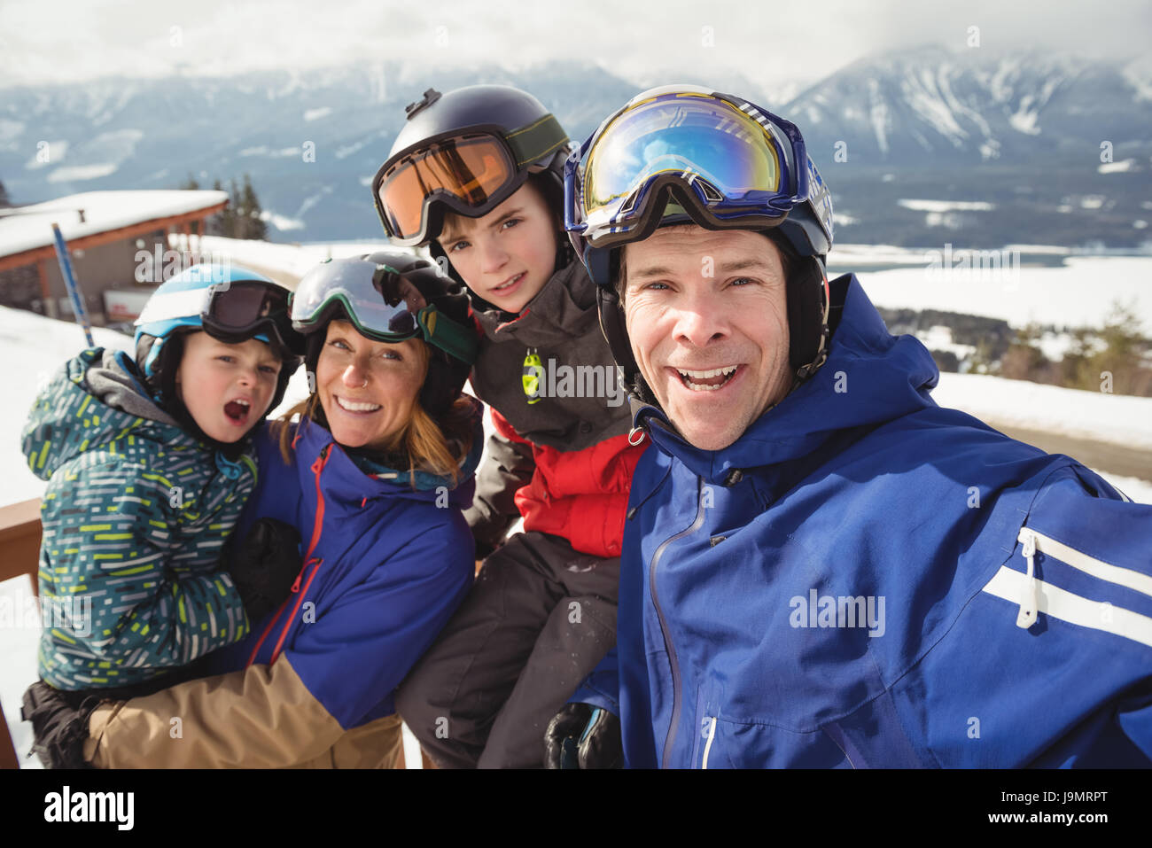 Portrait of happy family in skiwear during winter - Stock Image