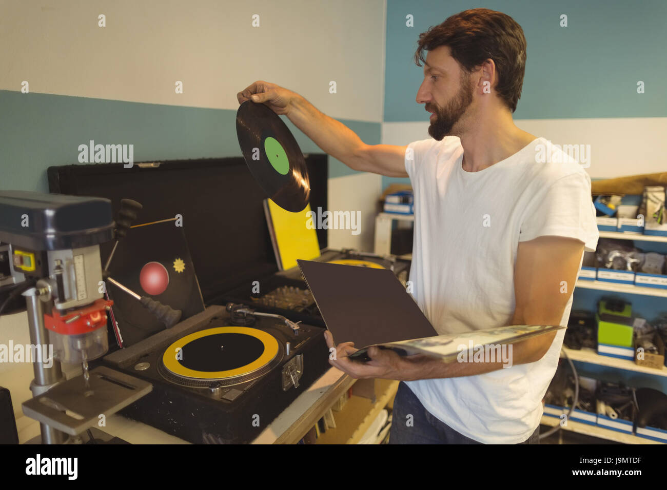 Worker holding record by turntable at bicycle workshop - Stock Image