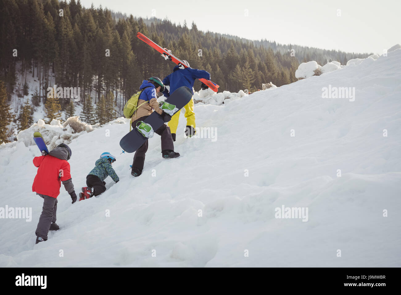 Family in skiwear climbing snowy alps during winter - Stock Image