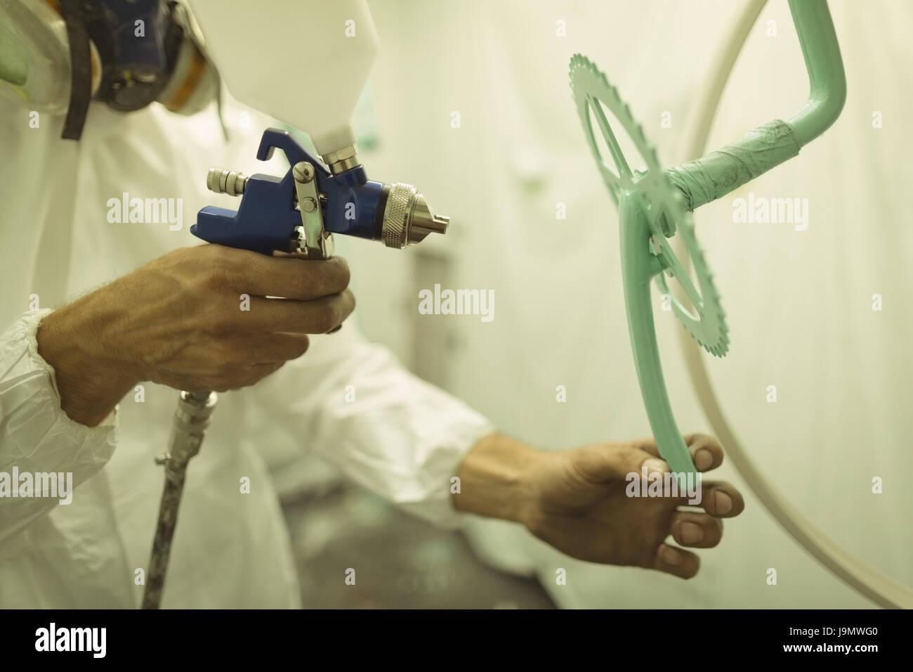 Painter painting bicycle gear through paint spray gun at workshop - Stock Image