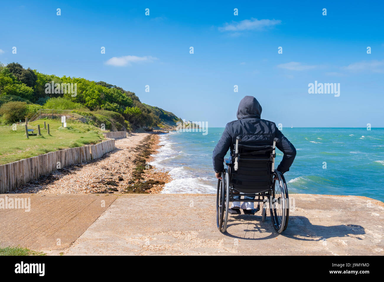 Disabled alone young man sitting in a wheelchair and looks at the sea. - Stock Image