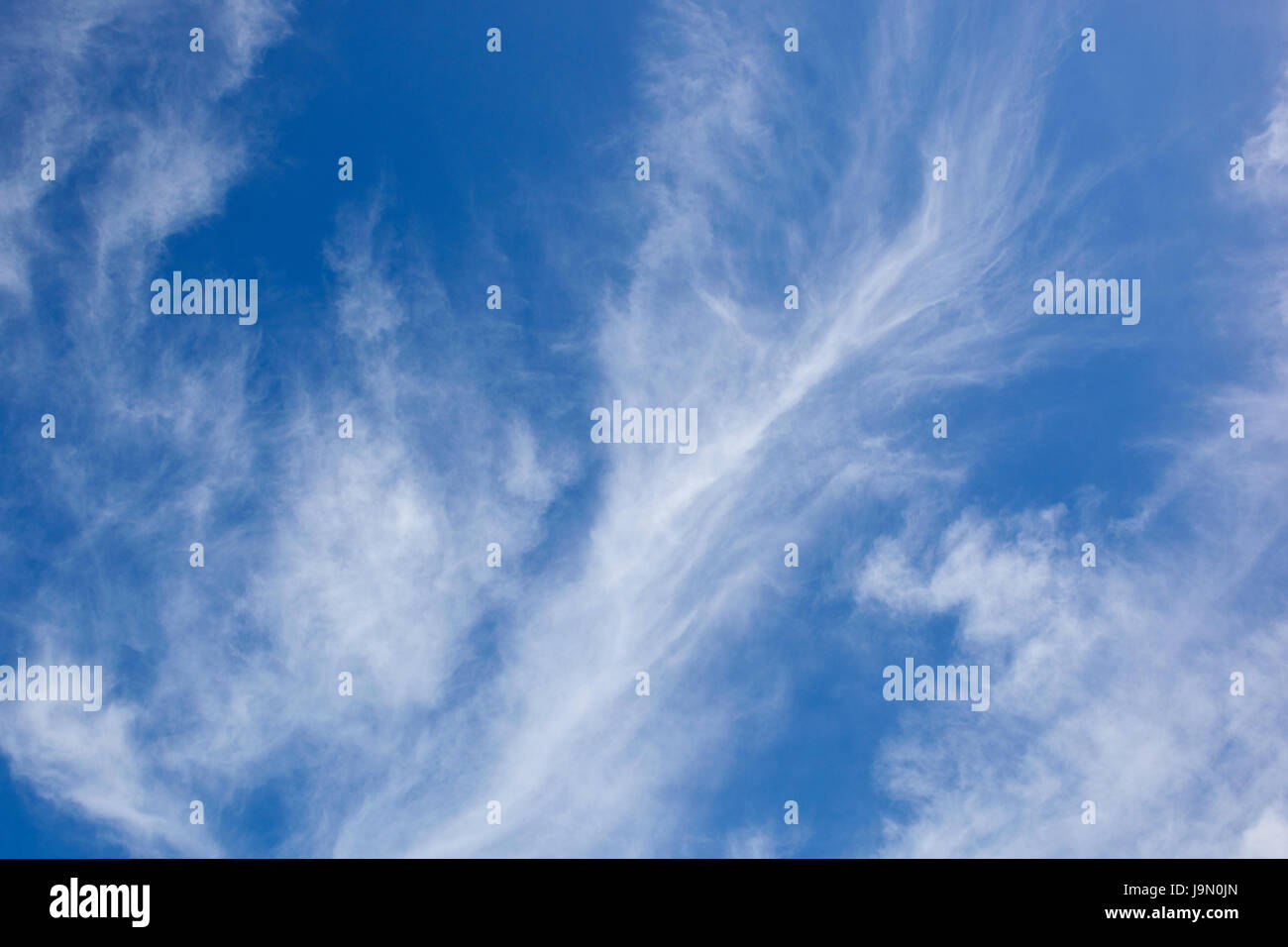 a blue sky background image with white wispy cloud in summer - Stock Image