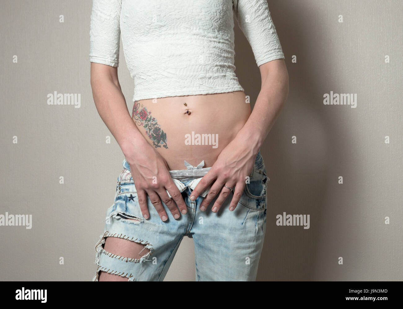 Young slim Caucasian woman wearing short knitted top with thumbs in belt line of open cut blue jeans, revealing - Stock Image