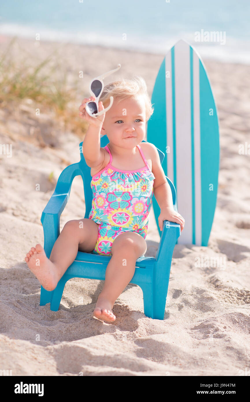 A one year old, baby girl sitting on a tiny beach chair at a sandy beach. She is holding sunglasses and wearing - Stock Image