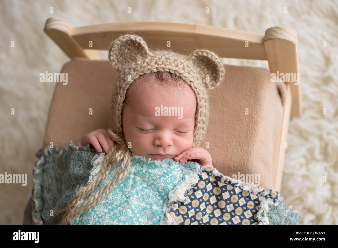Two week old newborn baby boy wearing a tan, crocheted, bear bonnet. He is  sleeping on a tiny, wooden bed and covered with a blue quilt. 4dfb0960369