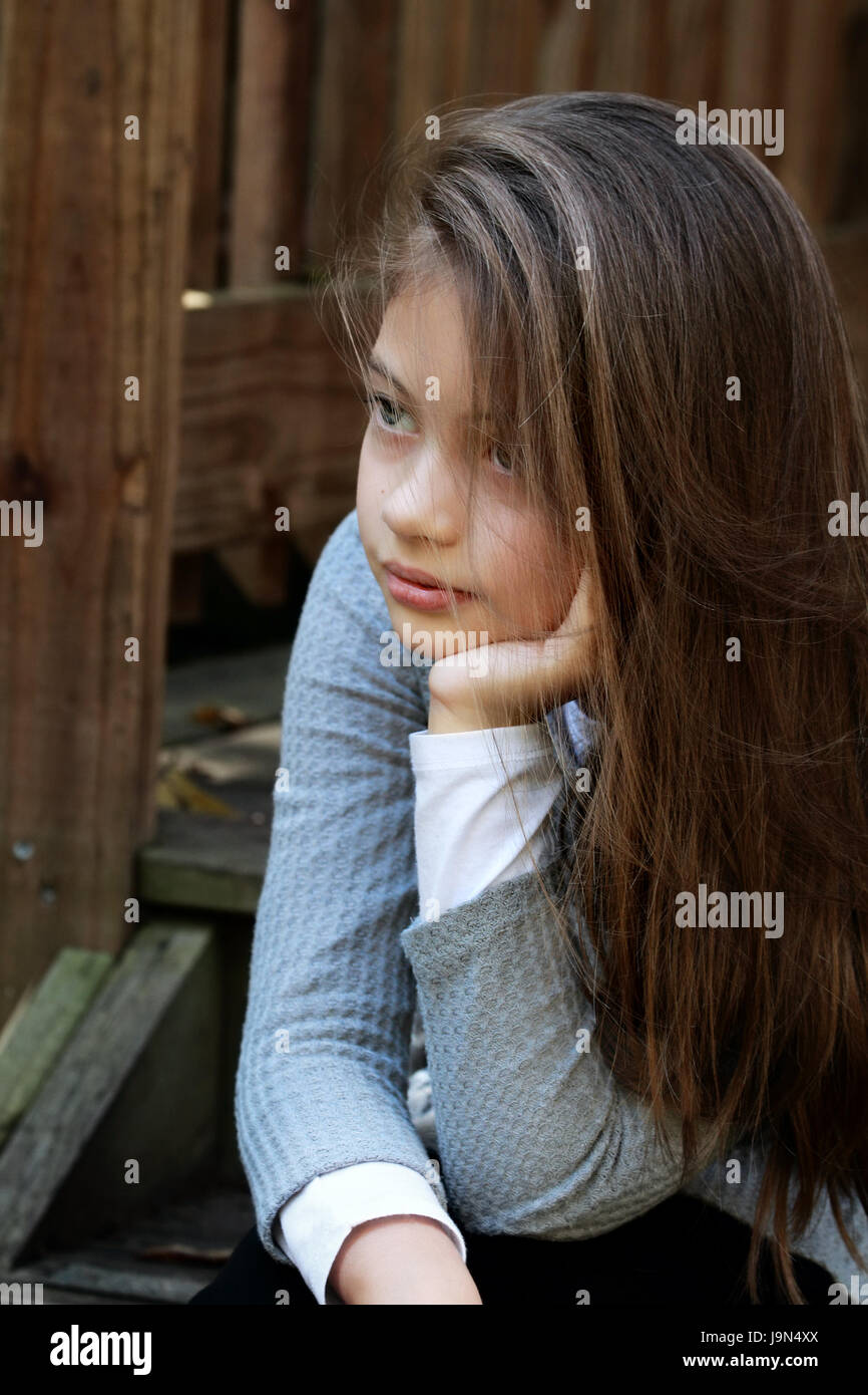 Young girl sitting on porch steps with long hair falling loosely around her face. Extreme shallow depth of field. - Stock Image
