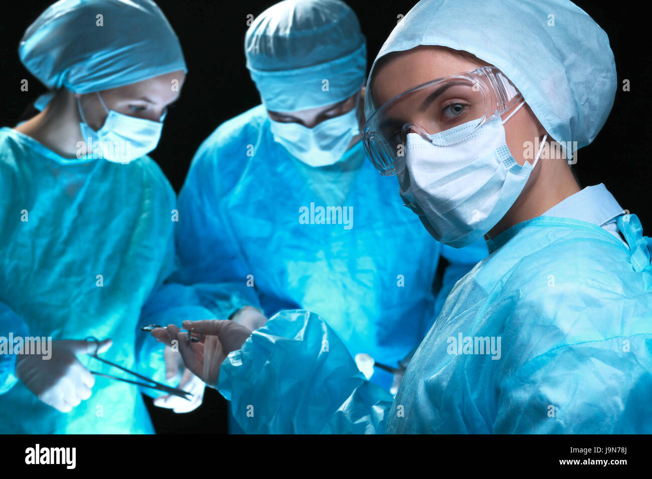 Three surgeons at work operating in surgical theater saving patient and looking at life monitor. Resuscitation medicine - Stock Image