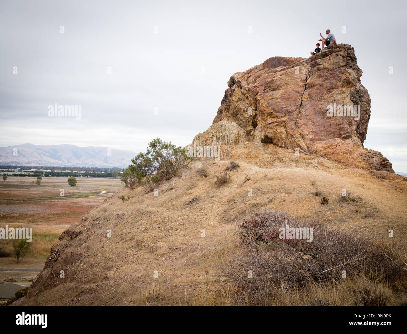 Father and son climbing peak in Coyote HIlls Regional Park in East Bay along San Francscio Bay near Newark or Fremont, - Stock Image