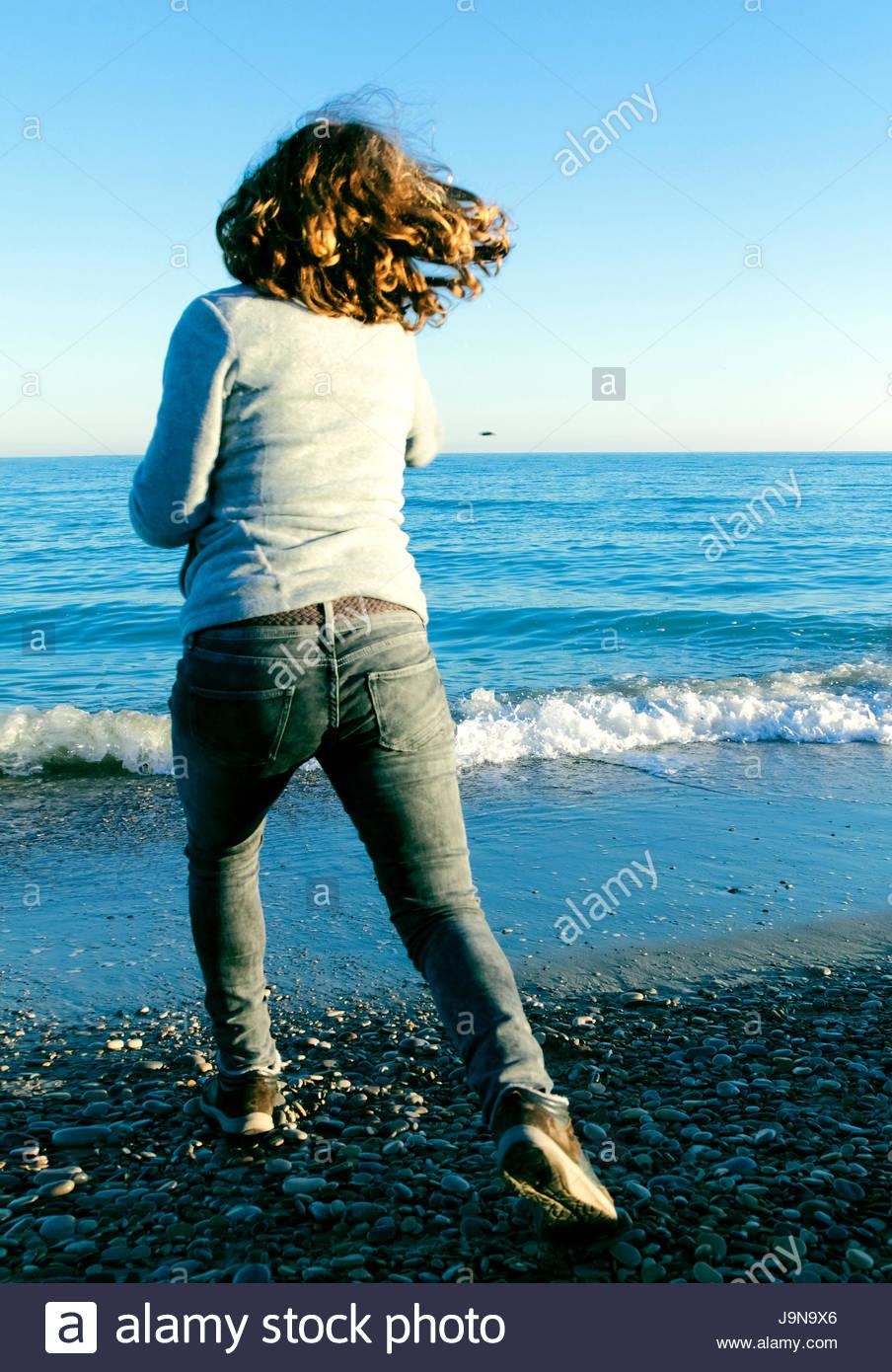 Chica lanzando una piedra al mar - Stock Image