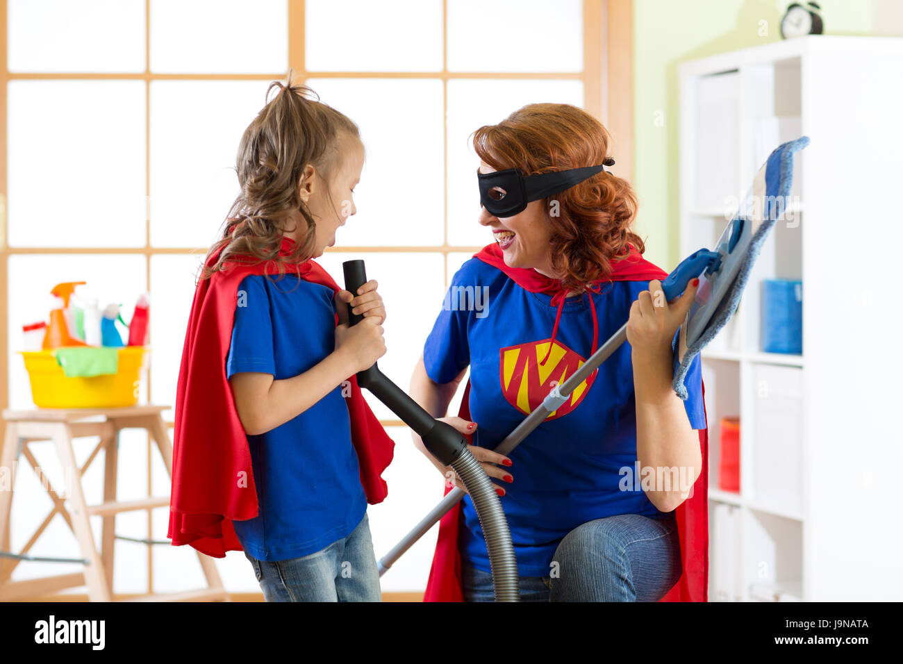 Happy woman with kid cleaning room and have a fun. Mother and child girl playing together. Family in Superhero costumes. - Stock Image