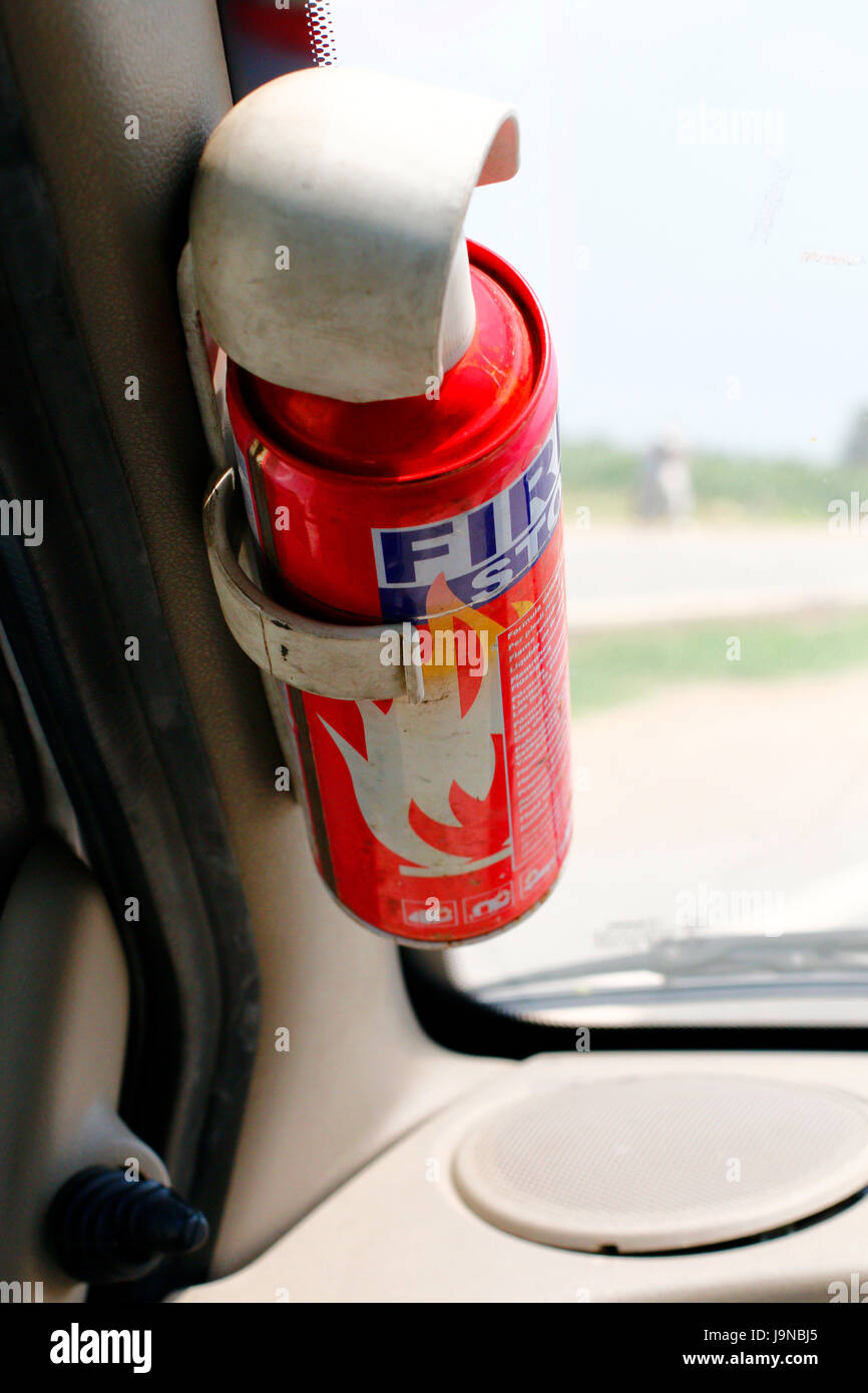 A fire extinguisher for emergency purpose in front seat of car - Stock Image