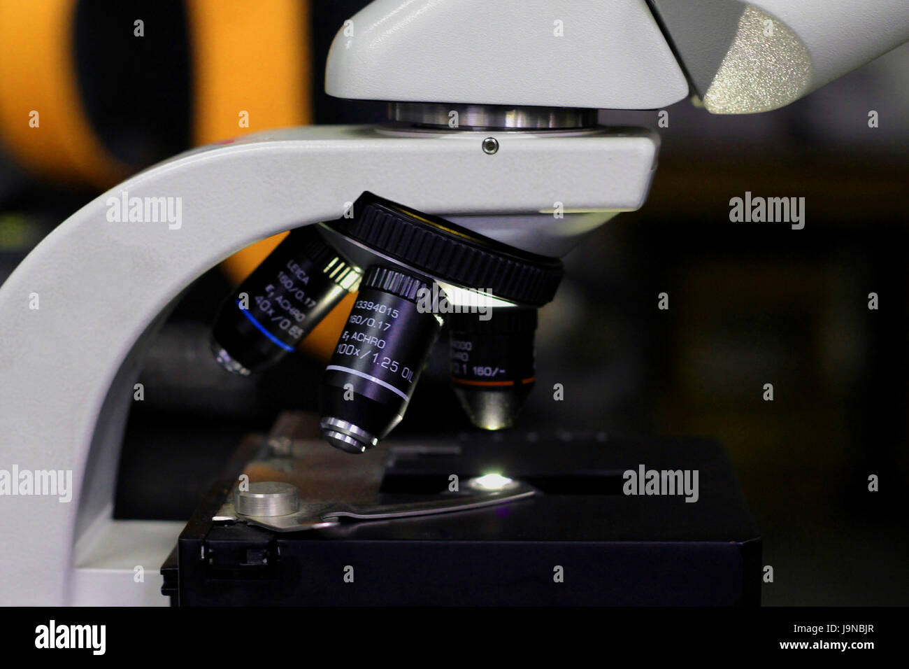side view of microscope in a research lab showing the objective lenses. Stock Photo