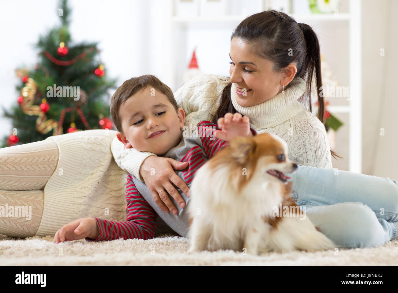 Family with dog at christmas tree - Stock Image