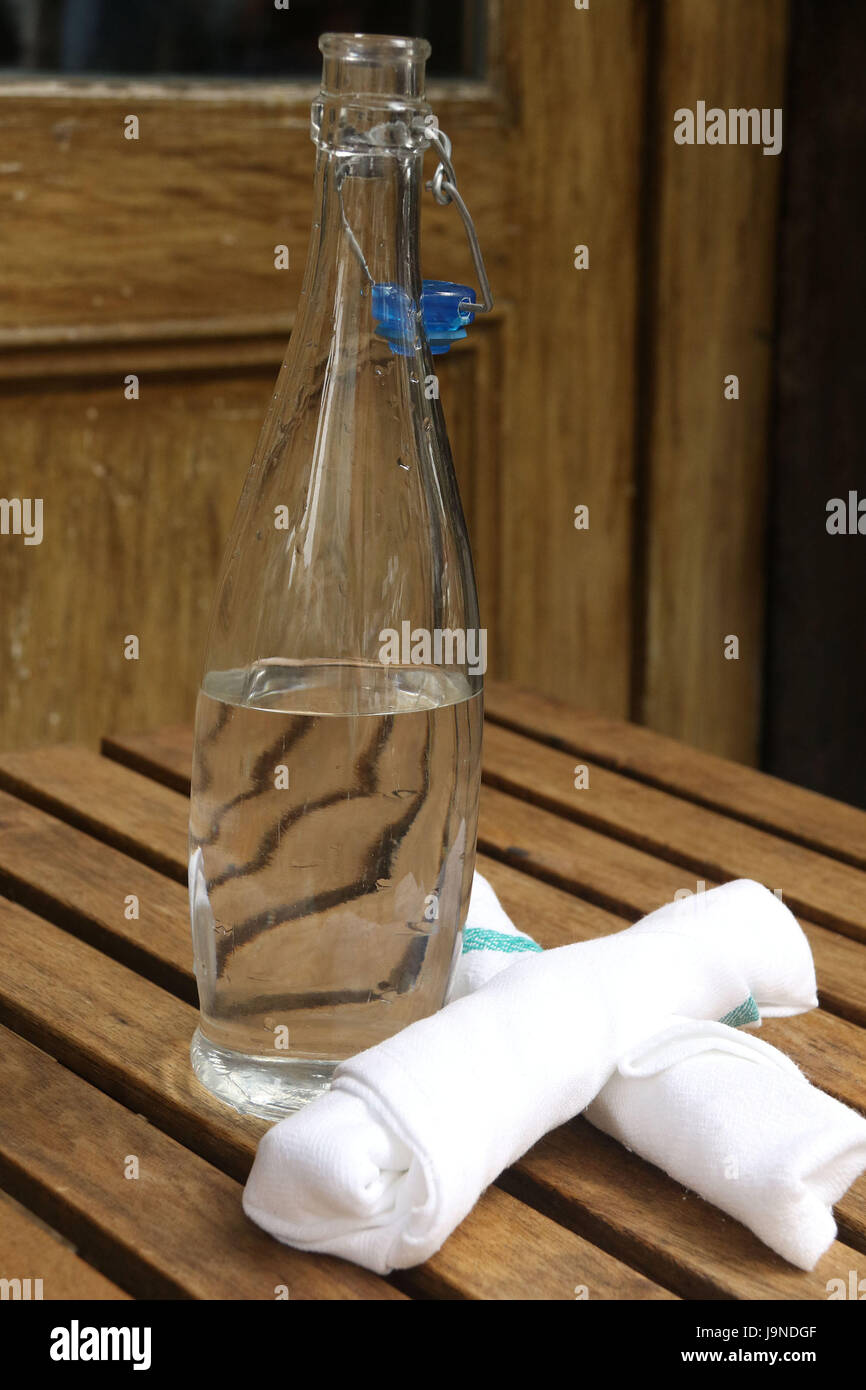 Bottled tap water with two napkins on wooden table - Stock Image