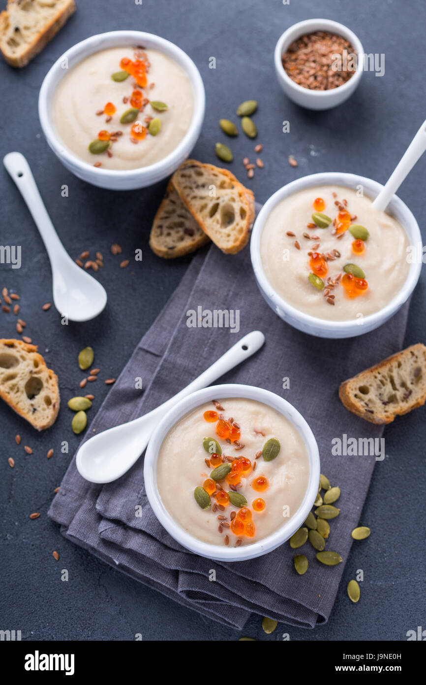 Top view of three bouls with creamy soup garnished with red caviar - Stock Image