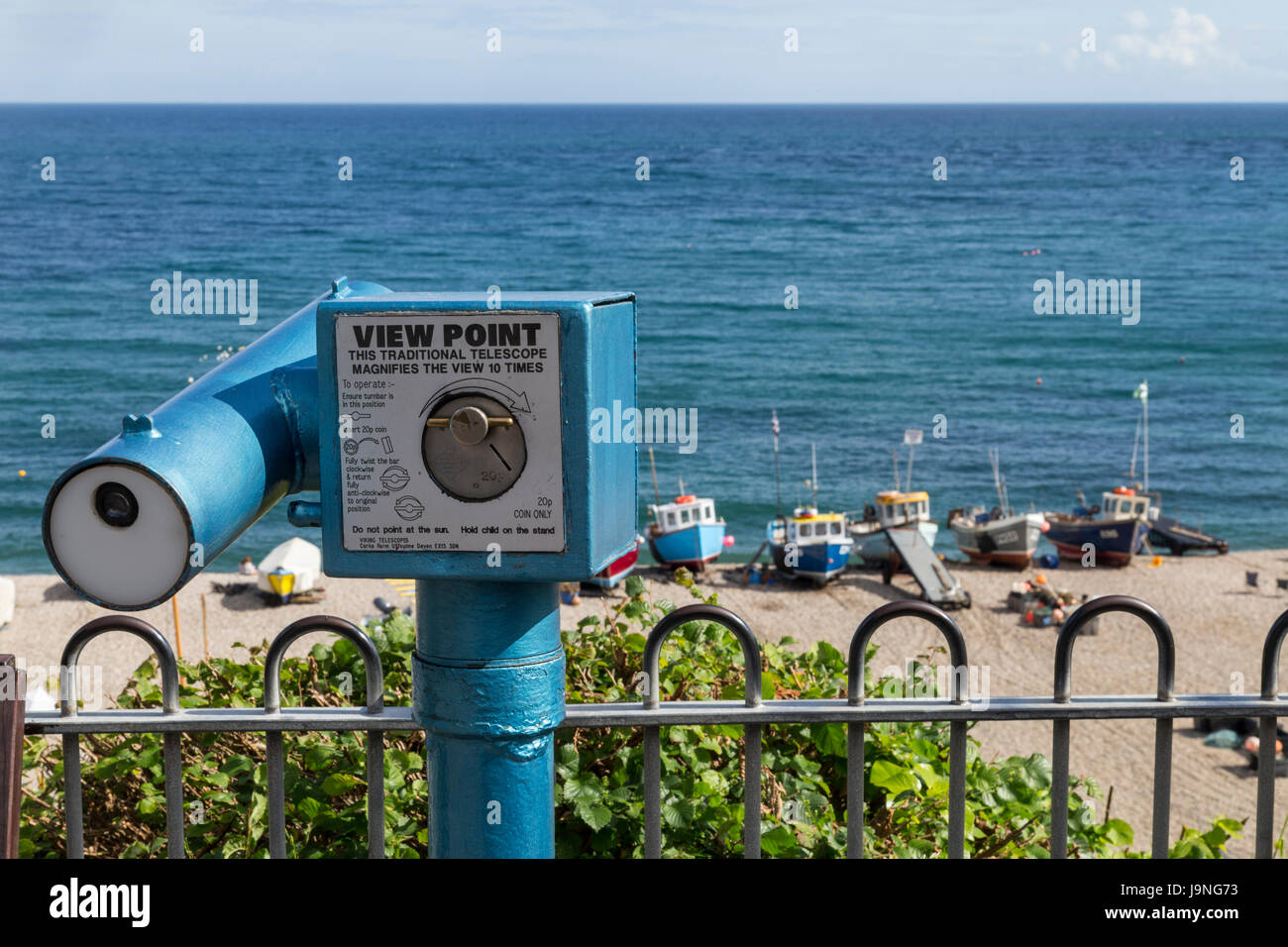 A viewpoint telescope ovelooking the bay at Beer, Devon, a pretty fishing village on the jurassic coast. - Stock Image