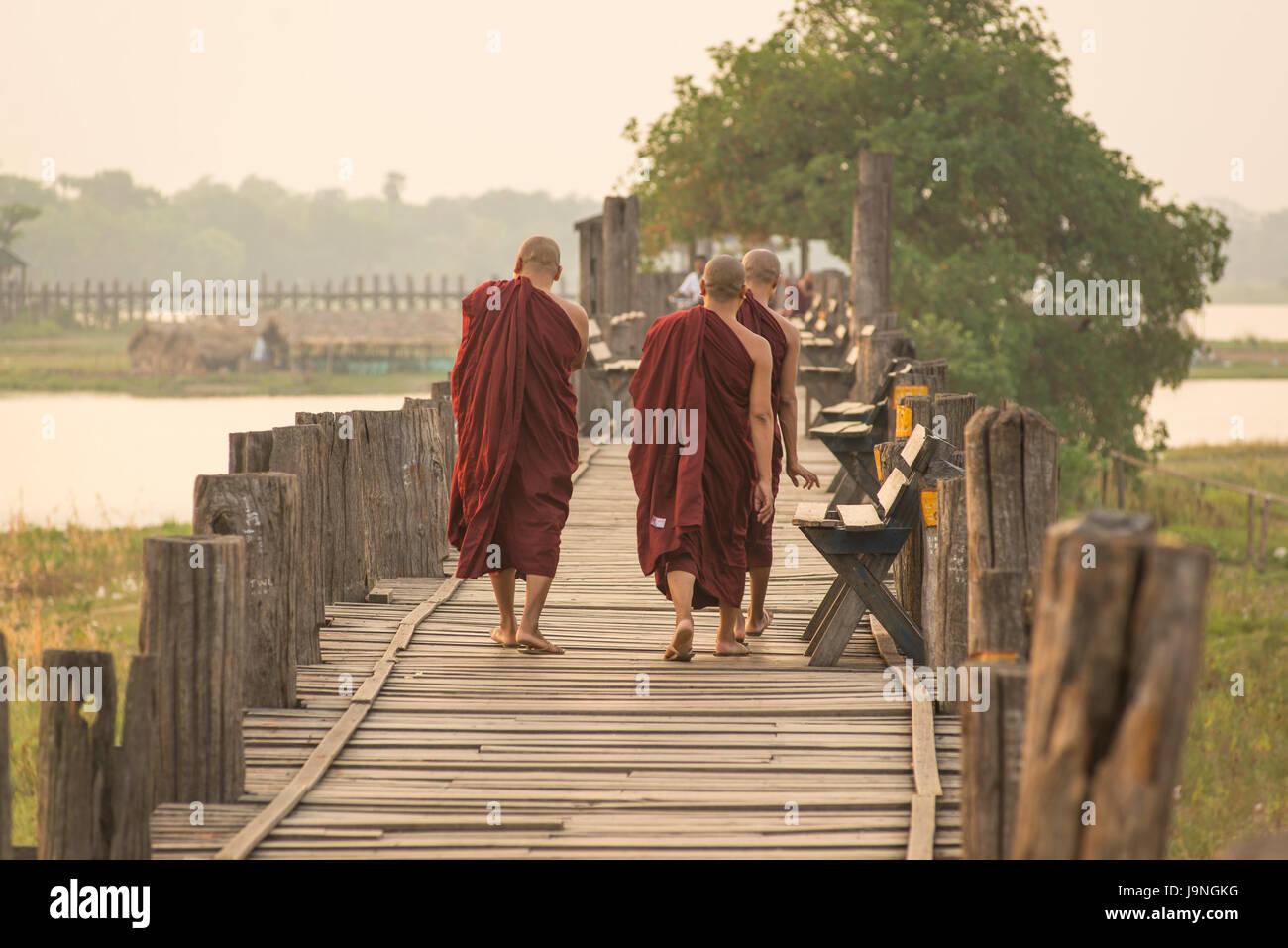 Monks waking at sunrise over U Bein Teak Bridge, Amarapura, Myanmar. - Stock Image