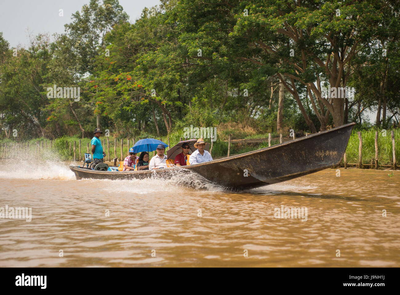 A motor boat carrying passengers on Inle Lake, Myanmar. Stock Photo