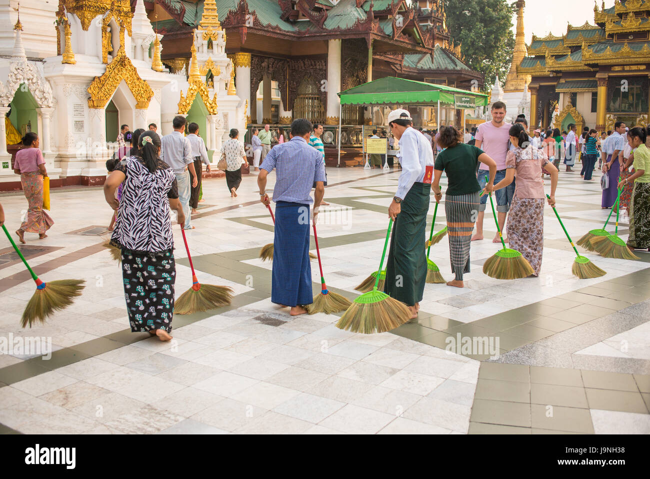 Cleaning the floor with the softest brooms ever. Shwedagon Pagoda, Yangon, Myanmar. - Stock Image
