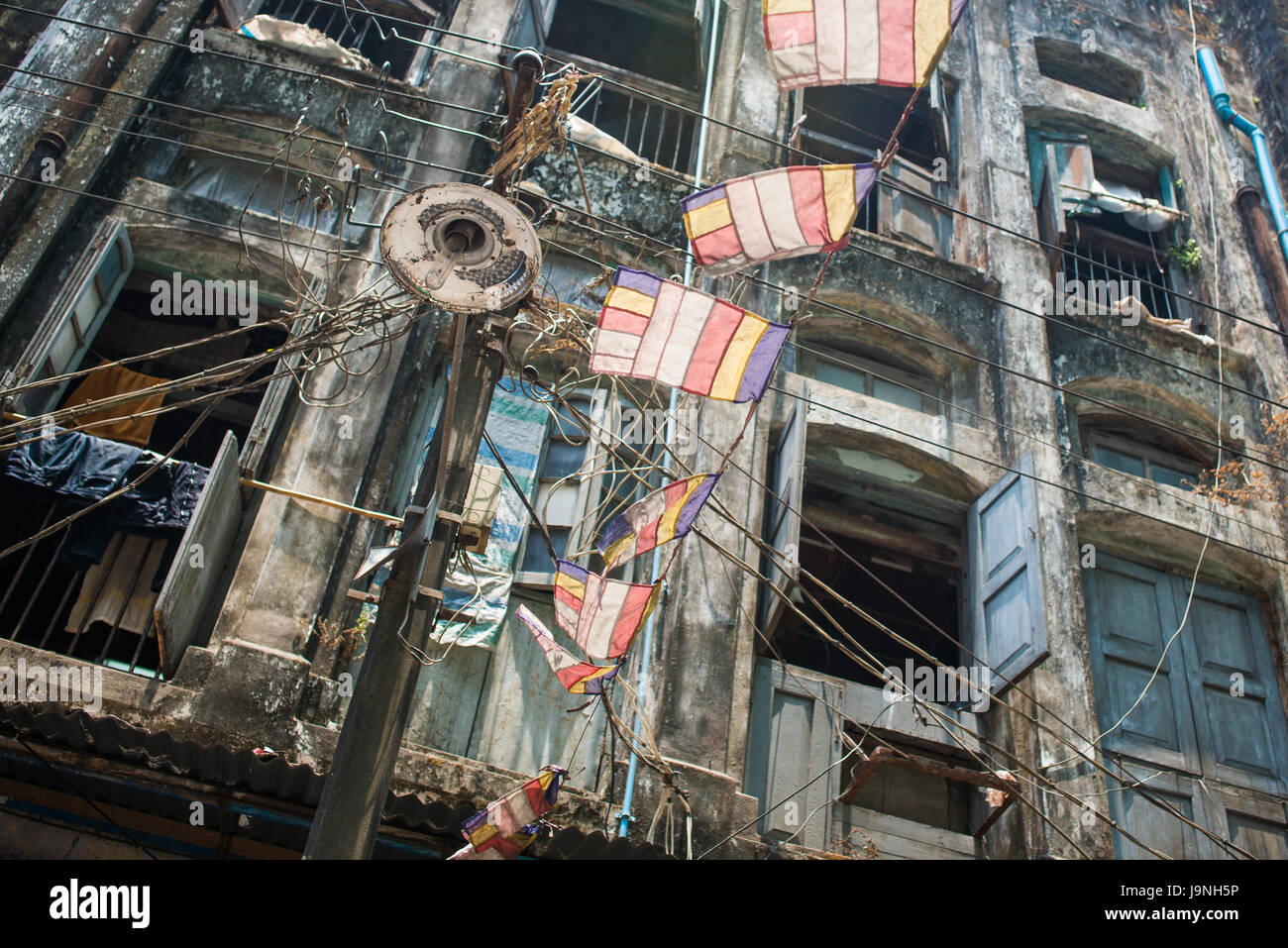 Looking up through a tangle of wires to a building in Yangon, Myanmar - Stock Image